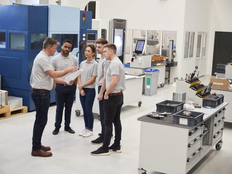 engineering-team-meeting-on-factory-floor-of-busy-37EK6PJ-scaled.jpg